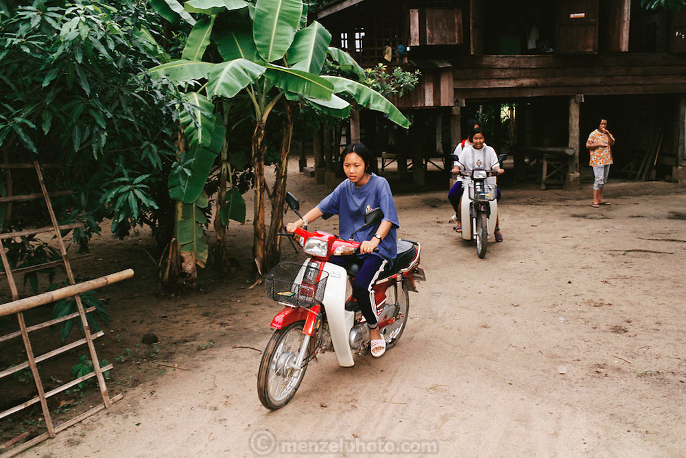 Jeeraporn Khuenkaew rides the family's most treasured possession?their motorcycle, on a Saturday along with some of her classmates who will join her at school for an agriculture class. Thailand. The Khuenkaew family lives in a wooden 728-square-foot house on stilts, surrounded by rice fields in the Ban Muang Wa village, outside the northern town of Chiang Mai, in Thailand. Material World Project.