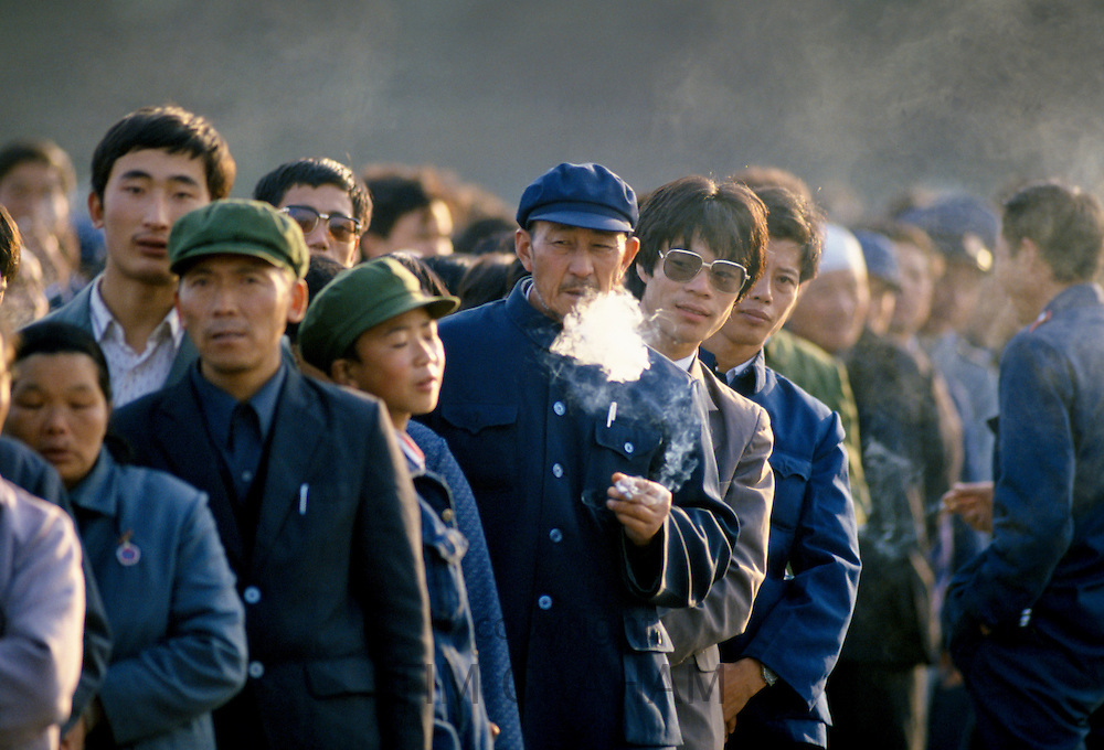 Chinese people, some smoking cigarettes, in Tiananmen Square in Peking, now Beijing, China in the 1980s