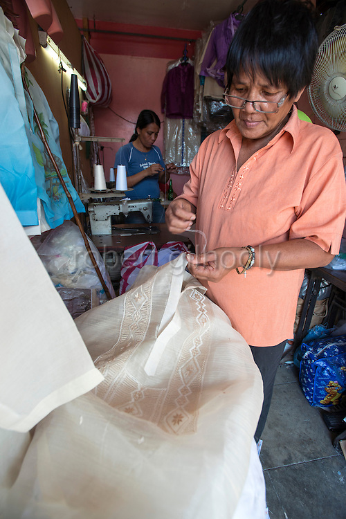 A  modiste sews buttons onto Photo a Barong Tagalog shirt inside Cress Lontoc's workshop in Taal, Batangas Province, the Philippines on Feb. 9, 2015. Barong have been a part of Philippine culture for over five centuries.  ROB GILHOOLY PHOTO