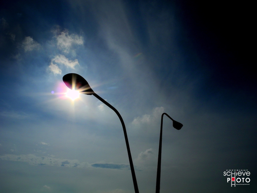 Sun peeks out from behind a street light.
