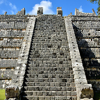 The Ossuary's Eastern Staircase at Chichen Itza, Mexico <br /> When The Ossuary was built between 900 – 1100 AD, it was designed with four staircases leading up to a sanctuary platform. The excellent condition of the eastern stairs shows the feathered serpents statues at the base and on top plus the carving of their coiled body ascending the masonry coping. Also notice the reliefs along the top three of the seven tiers.