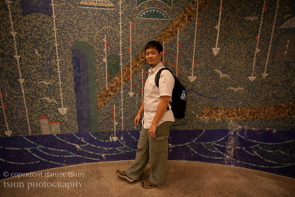 Daniel Tshin, photographer, pictured next to a wall of mosaic art in a subway station in Istanbul, Turkey