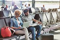 Mature woman working on her laptop,  husband is reading newspaper while waiting for boarding in airport