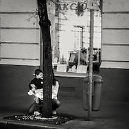 Young boy getting help to relief him self behind a tree in the streets of Budapest in Hungary