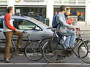 bicyclists and car waiting for traffic light Amsterdam Holland