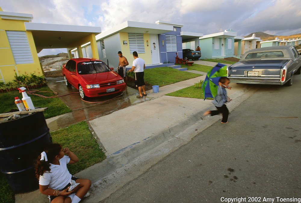 SANTA ISABEL, PR - MARCH 01: Jose Victor Colon washes his car outside his home in the federally subsidized Portal de la Reina development March 1, 2002 in Santa Isabel, Puerto Rico. Such housing, affordable and close to the interstate, is drawing young families away from Puerto Rico's small towns. Puerto Rico was an outpost of Spanish colonialism for 400 years, until the United States took possession in 1898. Today Puerto Rico's Spanish-speaking culture reflects its history - a mix of African slaves, Spanish settlers, and Taino Indians. Puerto Ricans fight in the U.S. armed forces but are not entitled to vote in presidential elections. They passionately debate their relationship with the U.S. with about half the island wanting to become the 51st state and the other half wanting to remain a U.S. commonwealth. A small percentage feel the island should be an independent country. While locals grapple with the evils of a burgeoning drug trade and unchecked development, drumbeats still drive the rhythms of African-inspired bomba music. (Photo By Amy Toensing) _________________________________<br /> <br /> For stock or print inquires, please email us at studio@moyer-toensing.com.