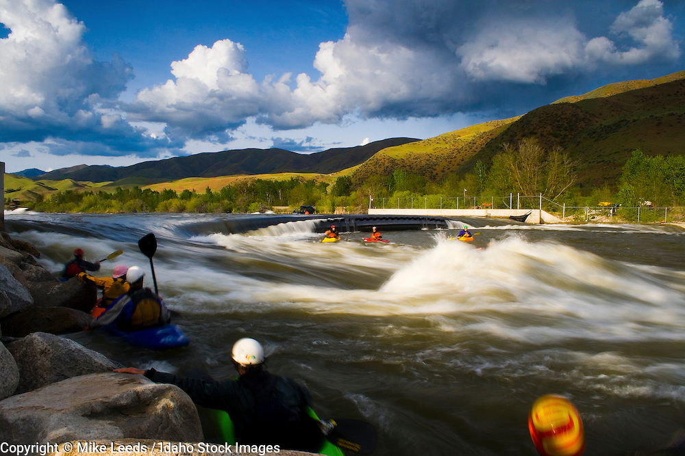 Kayakers in the line up wait there turn on a perfect day at the Bladder Wave on the Main Payette River in Idaho.