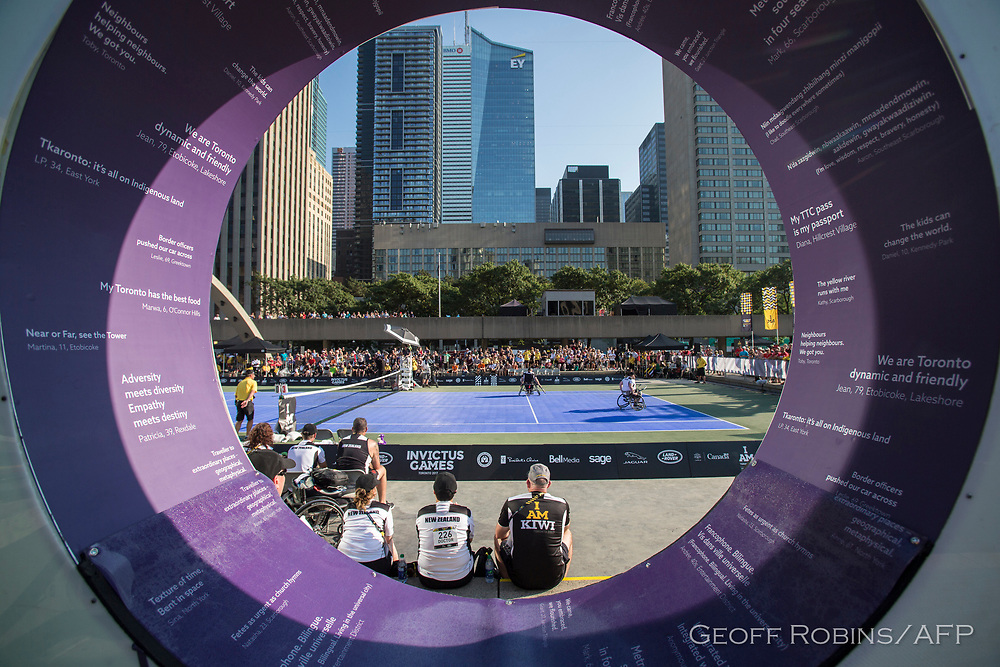 """In a view through the """"O"""" of the large Toronto sign in Nathan Phillips Square in Toronto, Ontario New Zealand takes on the United States in the Invictus Games Tennis competition in September 24, 2017."""
