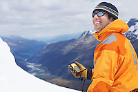 Mountain climber holding compass in snowy mountains