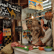 This shop was the only shop in the medina that sold camel meat.  How many places in the world would you see a camels head hanging in a food shop where they are butchering meat for you?  It's places like this that make this city truly unique and such a pleasure to visit.<br /> <br /> The Holy City of Fez, a jewel of Spanish-Arabic civilization, is an outstanding and well-preserved example of an ancient capital of the Almoravids and the Almohads in the North African context, despite the destruction of the city and the transfer of the capital to Rabat. The Medina of Fez in its old, densely packed monuments - madrasas, fondouks, palaces, residences, mosques and fountains - is the memory of the capital founded in year 192 of the Hegira (808) by Idriss II.<br /> <br /> The ancient city, home to the oldest university in the world, is composed of two distinct centres. One is the quarter of the Andalous, a population that fled from the Umayyad masters of Cordoba and who came to settle definitively on the right bank of the Fez. The other is the quarter of the Quarawiyyia, a people emigrated from Kairouan in the 11th century who chose the left bank of the river to develop their activities.<br /> <br /> Despite the destruction of a considerable part of the city by the Almoravids, the dynasty that took power in the 11th century, the two quarters grouped around two major monuments, the Jama el Andalous (the Mosque of the Andalusians) and the mosque of El Karaouiyne, have preserved their identities intact in the old city of Fez el Bali.<br /> <br /> In the 13th century, after the Merinid conquest, when the city found itself constrained within its walls, a new city, Fez el Jedid, was founded directly to the west, in ah 674 by the sultan Abou Youssouf. It replaced Marrakesh as the capital of the kingdom. In the 14th century a Jewish quarter, the Mellah, was joined to the newly founded city. The urban fabric and the principal monuments in the Medina date from this period.<br /> <br /> Since then, the twin cities have led a symbiotic existence