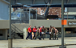 30 August, 2005. New Orleans Louisiana. Hurricane Katrina aftermath. <br /> Army medevacs unload an injured man saved from the catastrophic floods to the makeshift hospital triage unit set up at the Superdome.<br /> Photo Credit: Charlie Varley/varleypix.com