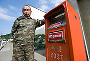 Jun Sasaki stands by the only post box in the Shizugawa district of Minami Sanriku, Japan on Tuesday 24 May 2011. Seven of the 15 post offices in the Ishinomaki catchment area -- which includes Minami Sanriku -- were destroyed by the March 11 disasters. .Photographer: Robert Gilhooly
