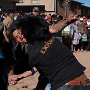 Police watch over one on one fighting between rival villagers in the streets of Macha during the Tinku Festival. Macha, Bolivia, 4th May 2010, Photo Tim Clayton ..Each May, up to 3000 thousands indigenous Bolivian indians descend on the isolated mountainous village of Macha 75 miles north of Potosi in the Bolivian Andes. The 600 year old pre-hispanic Bolivia Festival of Tinku sees villagers from all over the region march into town to be pitted against each other in a toe to toe fist to fist combat.. They dance and sing in traditional costume and drink 96% proof alcohol along with chicha, a fermented beverage made from corn. Townspeople and sometimes the police oversee proceedings who often use tear gas to try and control the villages, whipped into a fighting frenzy by the dancing and alcohol, but as the fiesta goes on things often escalate beyond their control, with pitched battles between rival villages break out,  The blood spilt is an offering to the earth goddess - Pachamama - to ensure a good harvest for the coming year. Over the years dozens have died, yet the rite continues.