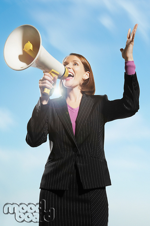 Smiling Mid-adult woman shouting through megaphone outside