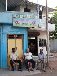 Men sitting outside children's nursery, Mumbai.