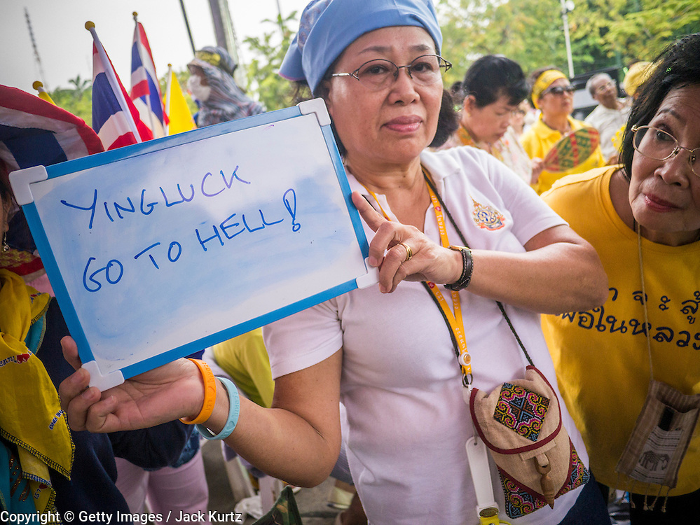 24 NOVEMBER 2012 - BANGKOK, THAILAND:  A woman carries a placard in opposition to Thai Prime Minister Yingluck Shinawatra during a large anti government, pro-monarchy, protest  on November 24, 2012 in Bangkok, Thailand. The Siam Pitak group, which sponsored the protest, cited alleged government corruption and anti-monarchist elements within the ruling party as grounds for the protest. Police used tear gas and baton charges againt protesters.       PHOTO BY JACK KURTZ
