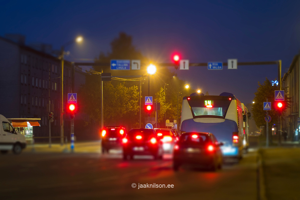 Red light of traffic signals stopped vehicles. Information and traffic signs in night. Street in Pärnu, Estonia.