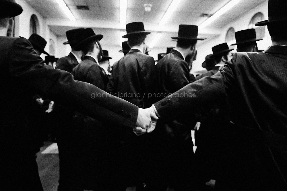 "Borough Park, Brooklyn, New York. Young jewish men performing hora, a circle dance around the groom, at the Rabbinical College Bobover Yeshiva on 48th street between 15th and 16th ave. The groom is Zvi Tauber, nephew of Ben Zion Halberstam, Gran Rabbi of the Congregation Shaarei Zion of Bobov, referred as ""Bobov 48"". Thousands of people, part of this community, were invited to celebrate the public wedding. Gianni Cipriano, cell +1 646 465 2168 (USA), +39 328 567 7923 (Italy), gianni@giannicipriano.com , www.giannicipriano.com"