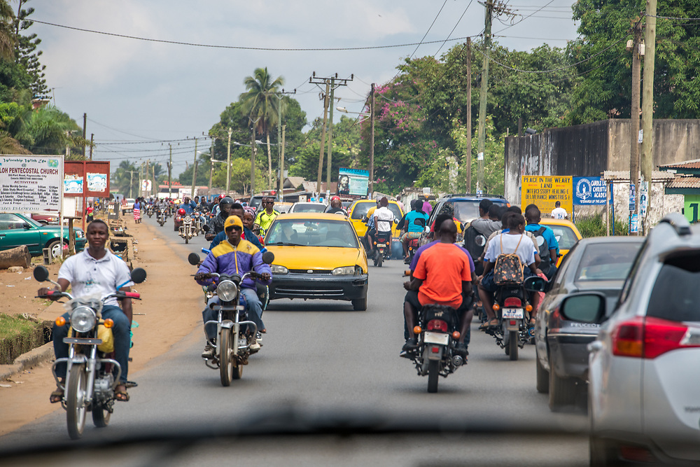 Men ride motorcycles through traffic in Ganta Liberia