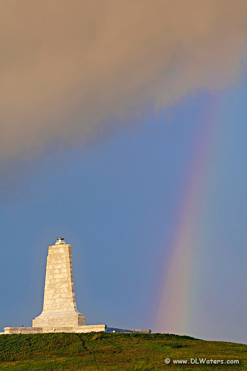 The Wright Brothers Memorial with storm clouds and a rainbow.