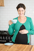 Pregnant woman drinking tea in kitchen