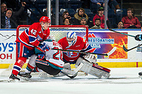 KELOWNA, CANADA - MARCH 13: Bailey Brkin #31 makes a save as Egor Arbuzov #42 of the Spokane Chiefs checks Leif Mattson #28 of the Kelowna Rockets  on March 13, 2019 at Prospera Place in Kelowna, British Columbia, Canada.  (Photo by Marissa Baecker/Shoot the Breeze)