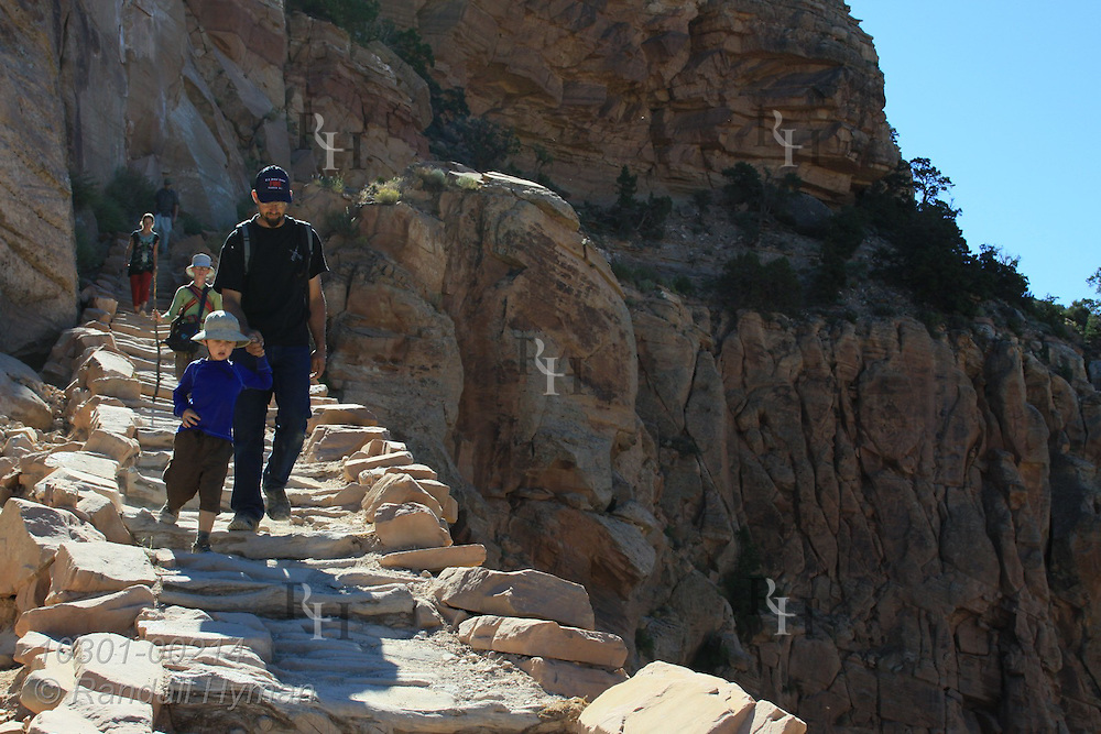 Father and young son hike down stone steps to Cedar Point on upper South Kaibab Trail; Grand Canyon National Park, Arizona.