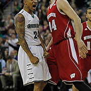 Green Bay's Keifer Sykes reacts in front of Wisconsin's Frank Kaminsky after dunking on the first possession against Wisconsin during the first half of an NCAA college basketball game Saturday, Nov. 16, 2013, in Green Bay, WIs. (AP Photo/Matt Ludtke)