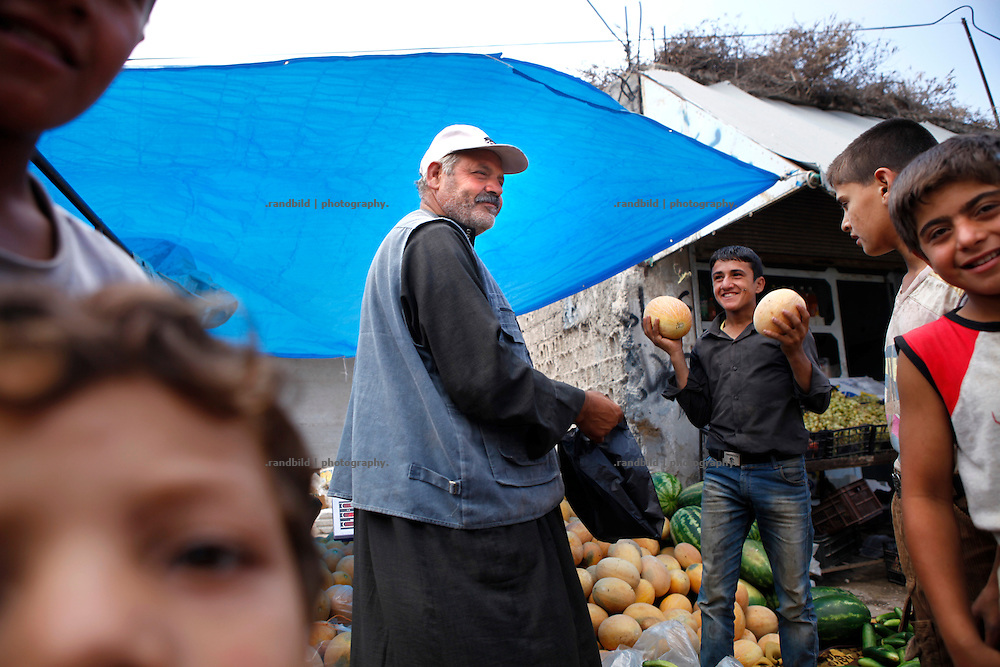 Vendor Omar (c) has received a delivery of melons for his vegetable and fruit shop located at the main street in Koreen.<br />