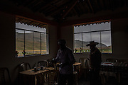 A farmer running a restaurant helps an employee to set up tables for the next customer aside San Jose reservoir, a dam built by Yanacocha from a pre-existing high Andean lagoon in the San Jose hamlet, Thursday, October 15, 2015.(Hilaea Media/ Dado Galdieri)