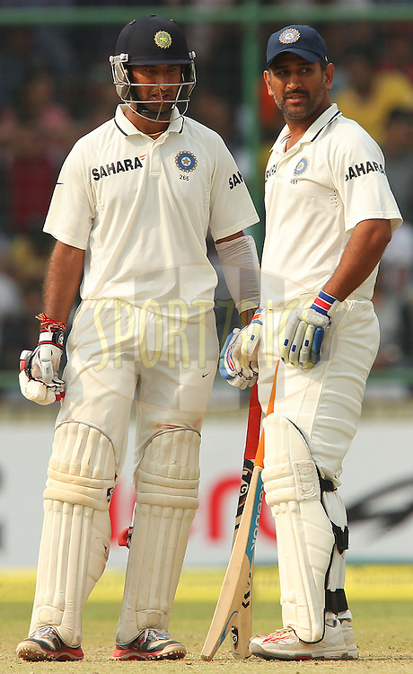 Cheteshwar Pujara of India  and MS Dhoni of India during day 3 of the 4th Test Match between India and Australia held at the Feroz Shah Kotla stadium in Delhi on the 24th March 2013..Photo by Ron Gaunt/BCCI/SPORTZPICS ..Use of this image is subject to the terms and conditions as outlined by the BCCI. These terms can be found by following this link:..http://www.sportzpics.co.za/image/I0000SoRagM2cIEc