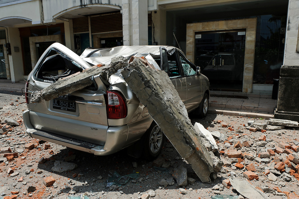 Earthquake damage in Simpang Siur, Kuta, Bali, Indonesia, 13/10/11. Part of the facade of a building broke away and badly damaged a car.