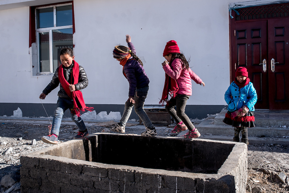 Students balance on the rim of Ngam-nak's trash pit during a break from classes. Ngam-nak, Tibet (QInghai, China) serves as a school for Tibetan nomadic children, who are dropped off by their parents and spend 8 months a year in the remote settlement until they have completed a basic level of education. Staffed by a handful of teachers and cooks, there are no other activities in Ngam-nak apart from the school.