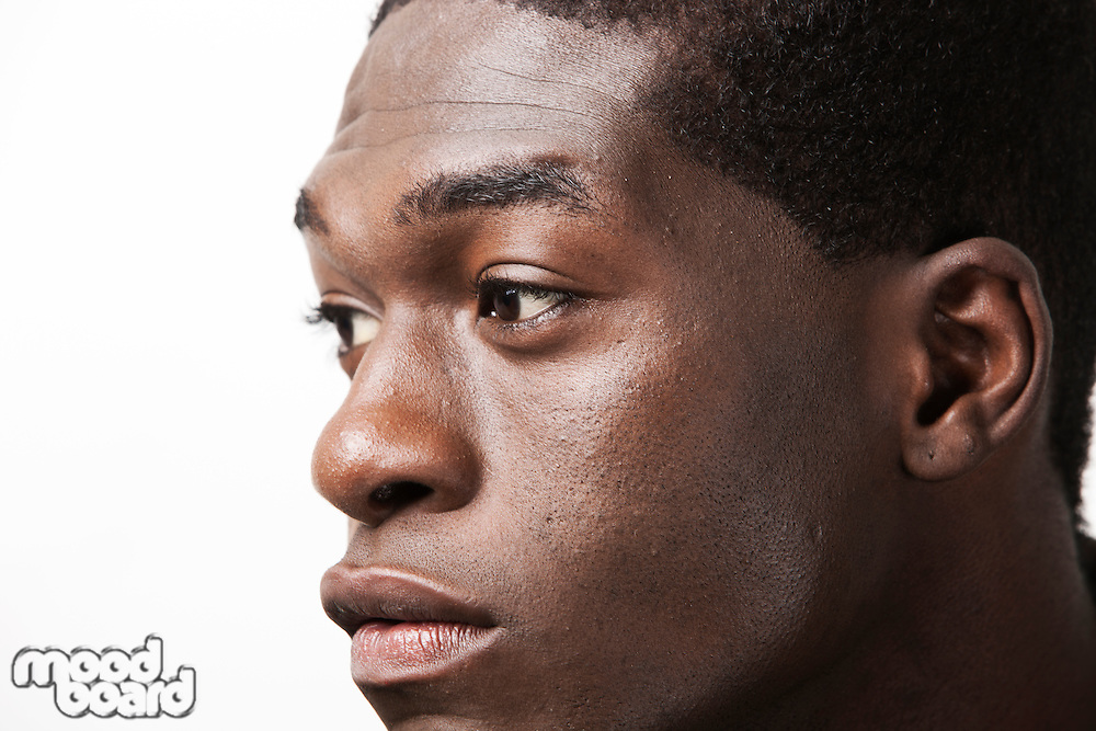 Close-up shot of thoughtful young man looking away against white background
