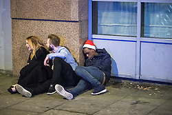 """© Licensed to London News Pictures . 24/12/2016 . Manchester , UK . A man wearing a Santa hat lies collapsed on the pavement outside Tiger Tiger , adjacent to vomit . Revellers out in Manchester City Centre overnight during 2016's second """" Mad Friday """" , named for historically being one of the busiest nights of the year for the emergency services in the UK . Photo credit : Joel Goodman/LNP"""