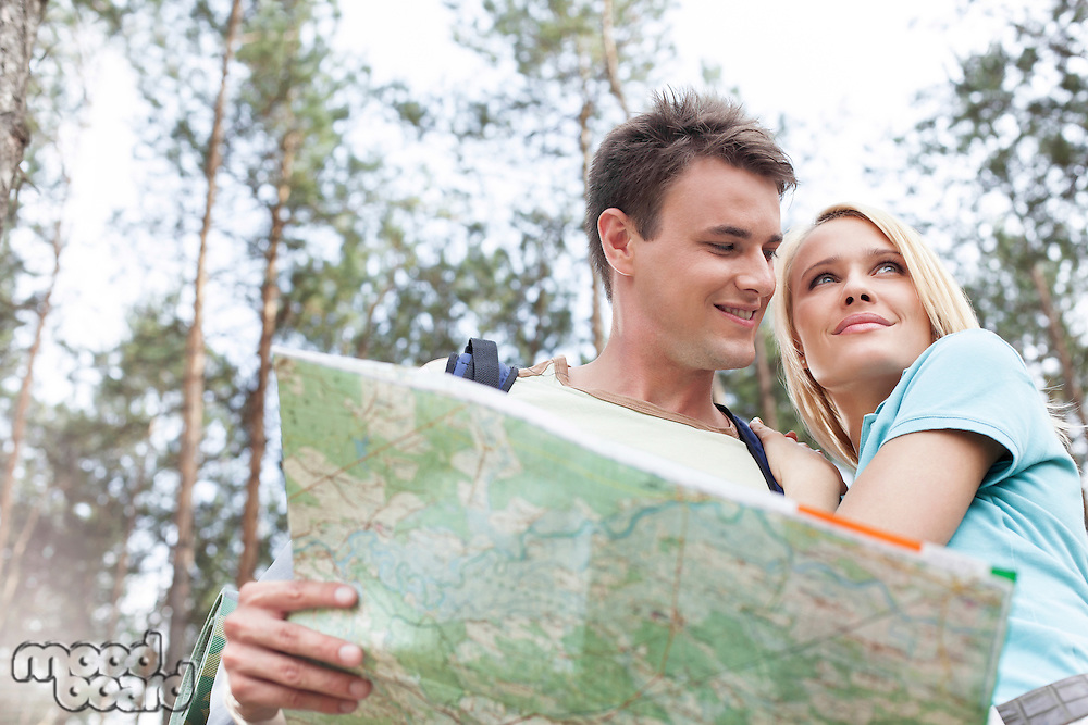 Happy young backpackers holding map in forest