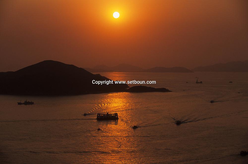 Hong Kong. sunset on the bay and  Sheung wan area-     /  coucher de soleil sur  baie et  /  loin de la folie du centre ville, au large de  l'ile Victoria, dès  la pointe de  Kennedy town on distingue déjà les premiers îlots.  Sheung wan      /  R94/8    L1102  /  R00094  /  P0001918