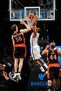 Brooklyn Nets' Alan Anderson (6) dunks a basket over Toronto Raptors' Tyler Hansbrough (50) and Chuck Hayes (44) during an NBA basketball game on Monday, March 10, 2014 at Barclays Center in New York. (AP Photo/Kathy Kmonicek)