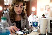 UConn President Susan Herbst checks messages on her cell phone at the Hyatt Regency in Dallas, Texas before watching her school compete in the NCAA Final Four on April 5, 2014. (Cooper Neill / for The New York Times)