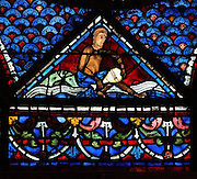 A man taking water from the river with a jug, from the donor window of the water sellers, from the Life of Mary Magdalene stained glass window, 13th century, in the nave of Chartres cathedral, Eure-et-Loir, France. Chartres cathedral was built 1194-1250 and is a fine example of Gothic architecture. Most of its windows date from 1205-40 although a few earlier 12th century examples are also intact. It was declared a UNESCO World Heritage Site in 1979. Picture by Manuel Cohen