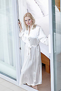 Portrait of beautiful young woman in bathrobe standing at balcony doorway