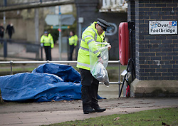 © Licensed to London News Pictures. 04/01/2018. Oxford, UK. A policeman looks in an evidence bag at scene where the body of a 16 year old boy was discovered next to the River Thames in Oxford yesterday evening. A man and a woman have been arrested after the victim was found with stab wounds at Friars Wharf, who later died in hospital. Photo credit: Peter Macdiarmid/LNP