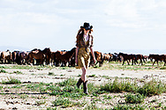Redhead young woman in ranch with horses, Nevada, United States