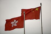 A Chinese national flag flies next to a Hong Kong SAR flag.