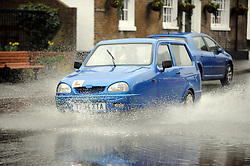 © Licensed to London News Pictures. 11/02/2014<br /> Robin Reliant driving into flood water in Eynsford High Street as the River Darent has burst its banks in Kent.<br /> The bad weather continues today (11.02.2014) flooding parts of Kent with high winds and more rain to come this week.<br /> Photo credit :Grant Falvey/LNP