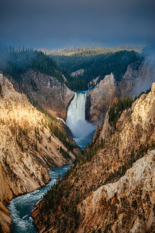 The Grand Canyon of the Yellowstone is lit up during sunrise in Yellowstone National Park, Wyoming