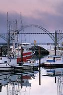 Fog at dawn over commercial fishing boats in harbor and Yaquina Bay Bridge, Yaquina Bay, Newport, Oregon Coast