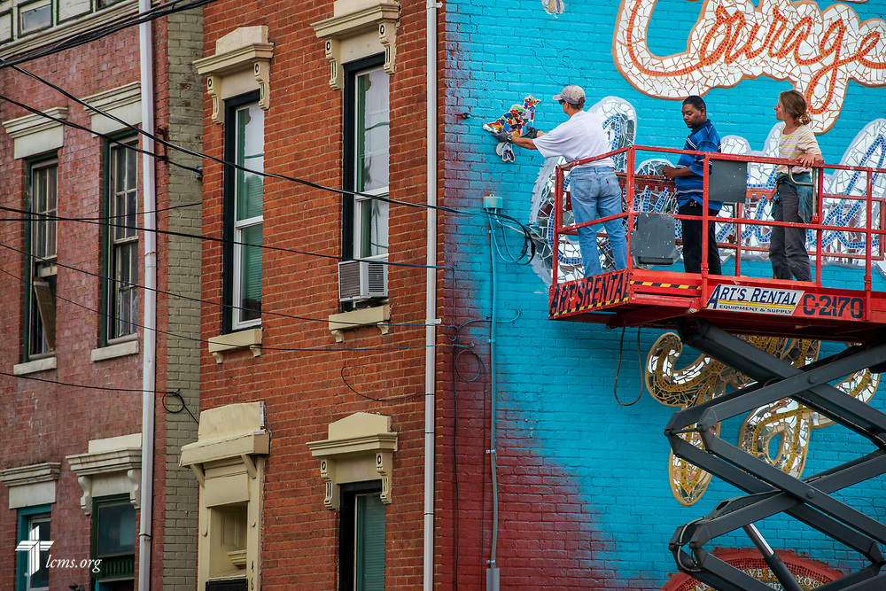 Artist Rachel Ziegler (right), volunteer Martha Gitt and Curtis Jones from Prince of Peace Lutheran Church in the Over-the-Rhine neighborhood of Cincinnati, work on a new mural on the side of Victoria's House of Hope, a transitional housing apartment building that is part of The Welcome Home Collaborative program, on Wednesday, May 16, 2018, in Cincinnati. Victoria, a young woman who volunteered her time at Prince of Peace Lutheran Church, made a wish to the Make-a-Wish Foundation to rehab the old building before she died of a brain tumor. Ziegler designed the mural and had attendees of the church and external community assist with the construction. LCMS Communications/Erik M. Lunsford