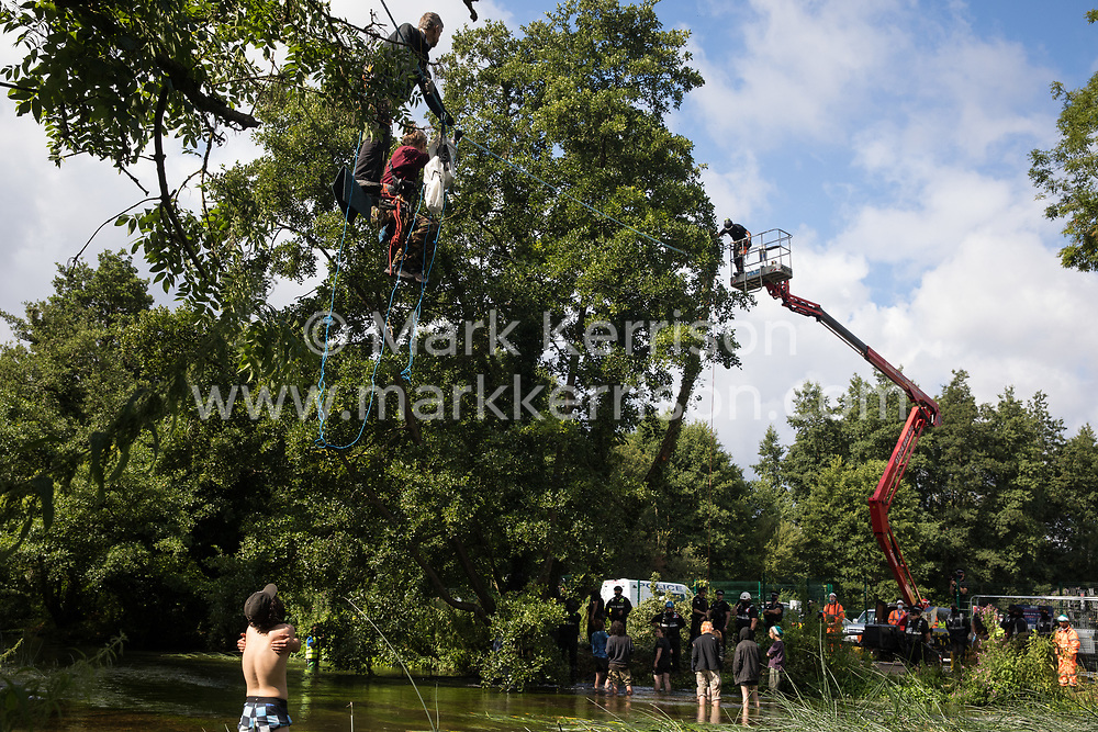 Denham, UK. 24 July, 2020. Larch (l) and Swan (r), environmental activists from HS2 Rebellion, try to communicate regarding safety with a tree surgeon working close to their line above the shallow river Colne attached to an ancient alder tree which they were trying to protect from destruction in connection with works for the HS2 high-speed rail link in Denham Country Park. 2020 is the Year of the Tree.