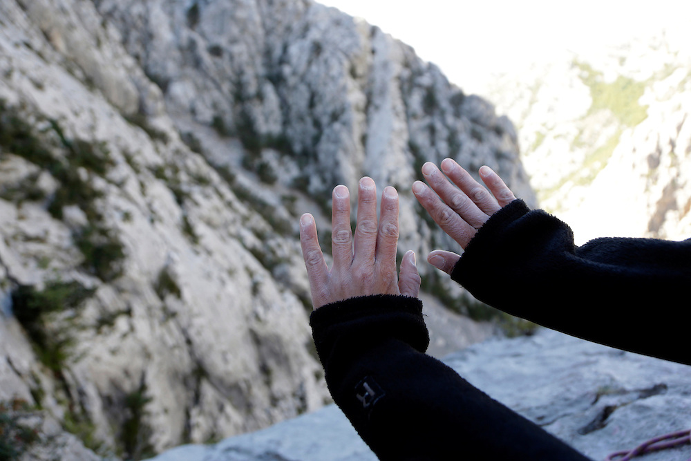 Climber's hands, white from magnesia, during climbing of the route 'Brid za Veliki Cekic', Paklenica National Park, Croatia.